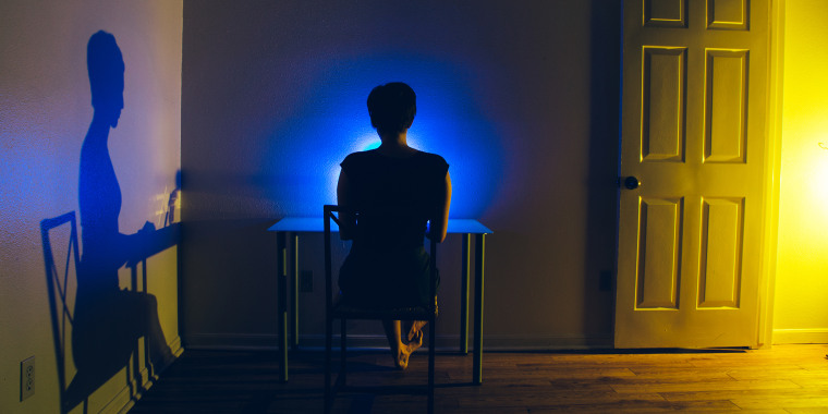 Woman at desk in dark room