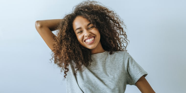 Portrait of woman with afro hair smiling with white wall background