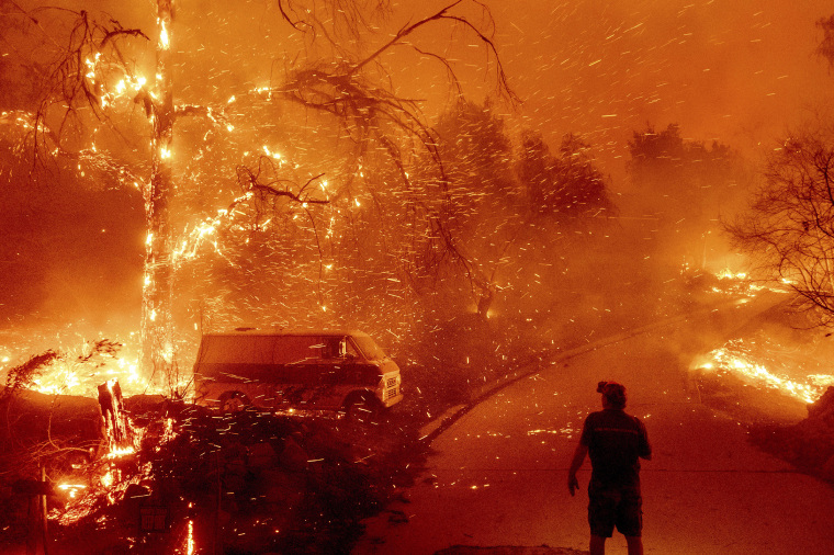 Bruce McDougal watches embers fly over his property as the Bond Fire burns through the Silverado community in Orange County, Calif., on Thursday, Dec. 3, 2020.
