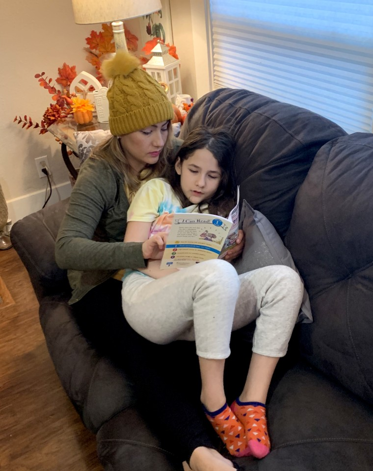 Image: Angelica Gonzalez and her daughter, Lolly, read on the couch at home.