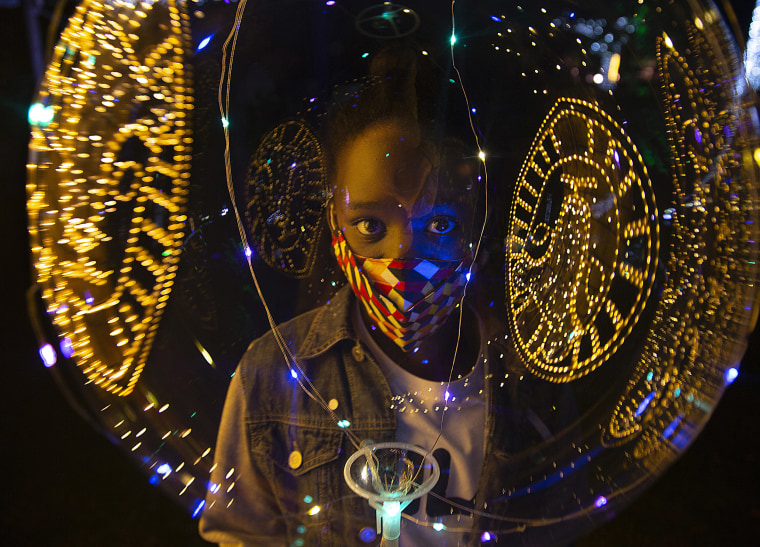 Image: Christmas lights are reflected on a ballon as a child wears a face mask to protect against coronavirus at the Johannesburg Zoo's Festival of Lights