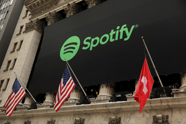 Image: FILE PHOTO: The Spotify logo hangs on the facade of the New York Stock Exchange with U.S. and a Swiss flag as the company lists it's stock with a direct listing in New York