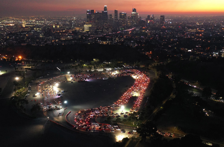 Image: Cars are lined up at Dodger Stadium for COVID-19 testing as dusk falls over downtown on Dec. 2, 2020 in Los Angeles.