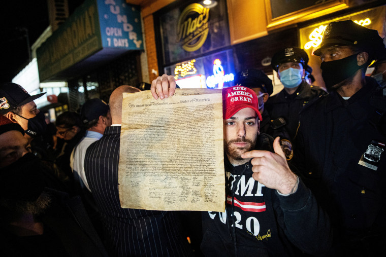 Image: A man holds a copy of the Declaration of Independence while people protest outside of the Mac's Public House after it closed down amid the coronavirus disease (COVID-19) pandemic in the Staten Island borough of New York City