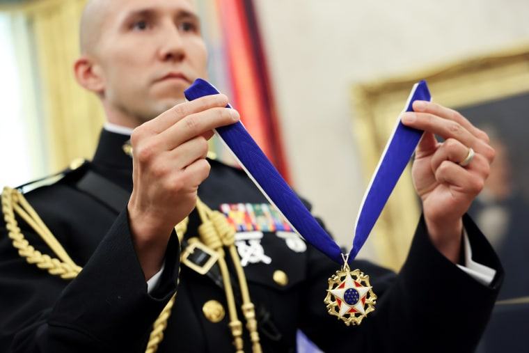 Image: A U.S. Marine military aide holds the Presidential Medal of Freedom for Trump to award to Holtz in the Oval Office at the White House in Washington