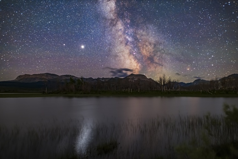 The galactic core area of the Milky Way over Maskinonge Pond in Waterton Lakes National Park, Alberta. Jupiter is the bright object at left, with Saturn dimmer to the left (east) of Jupiter. In the summer of 2020 the two planets were close together in the