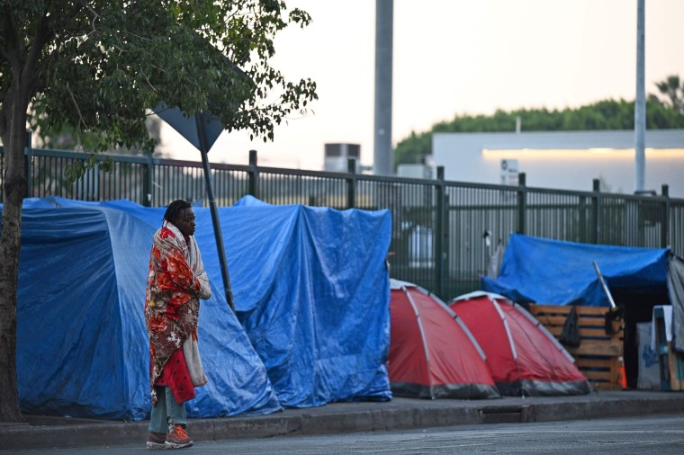 A homeless man stands outside tents on Skid Row on Nov. 25, 2020 in Los Angeles.