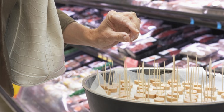 Mature woman taking sample in supermarket, mid section, close-up