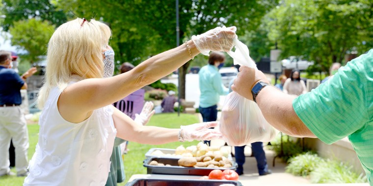 Pastor Susan Crowell hands out meals at Trinity Lutheran church in Greenville, South Carolina.