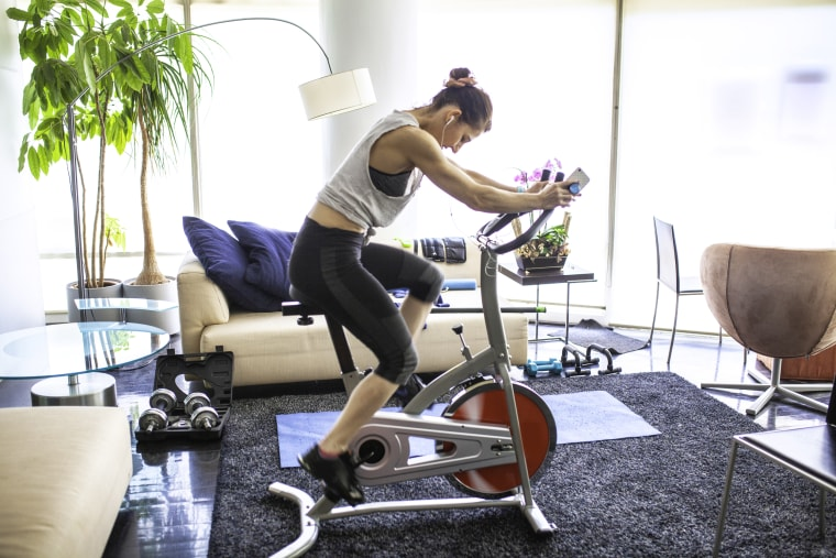 Home gym cycling indoors at living room. Shop the best spinning accessories for indoor cycling 2020 from Adidas, Athleta, Old Navy, Bandier, Theragun, Amazon, Walmart, Target and more.