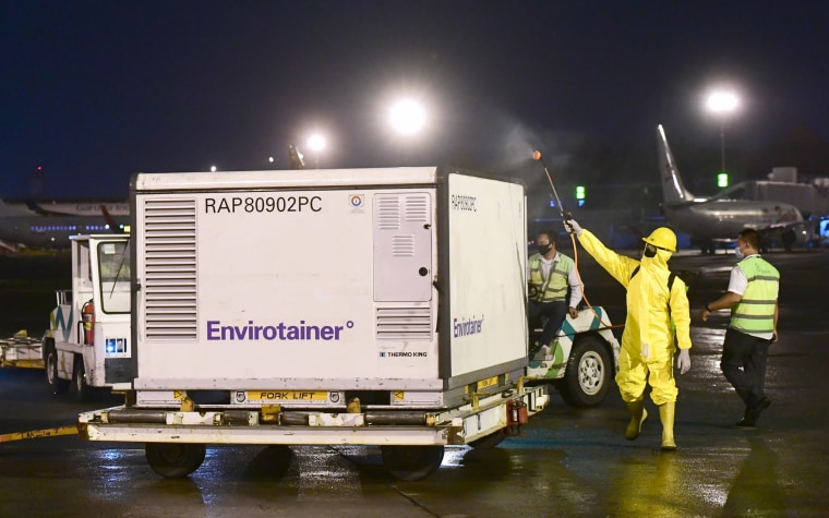 Image: Workers spray disinfectant over a container containing experimental coronavirus vaccines made by the Chinese company Sinovac, upon arrival at the Soekarno-Hatta International Airport in Tangerang, Indonesia,