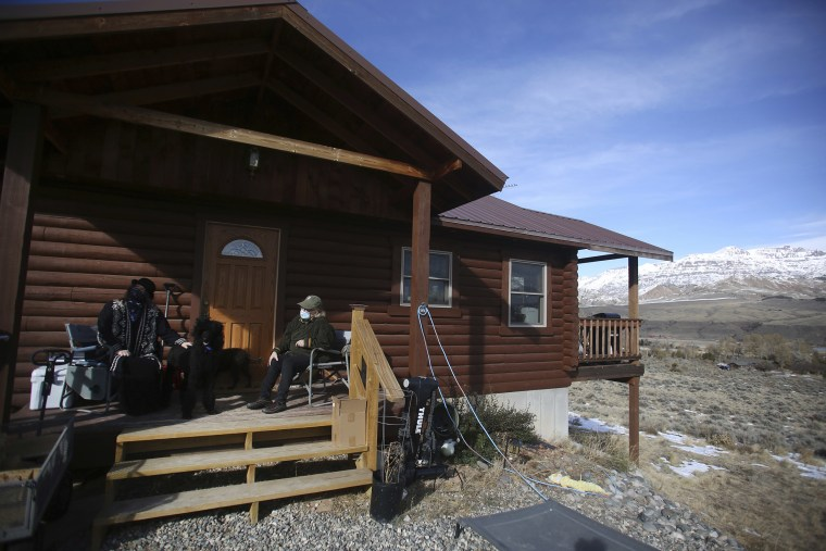 Image: Shannon Lastowski Monahan and Colin Monahan sit on the front porch of their home in Wapiti, Wyo.