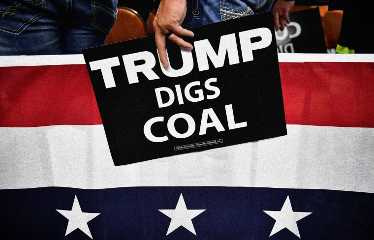 """Image: A supporter of President Donald Trump holds a sign that reads """"Trump Digs Coal"""" a rally in Charleston, W.V., on Aug. 21, 2018."""