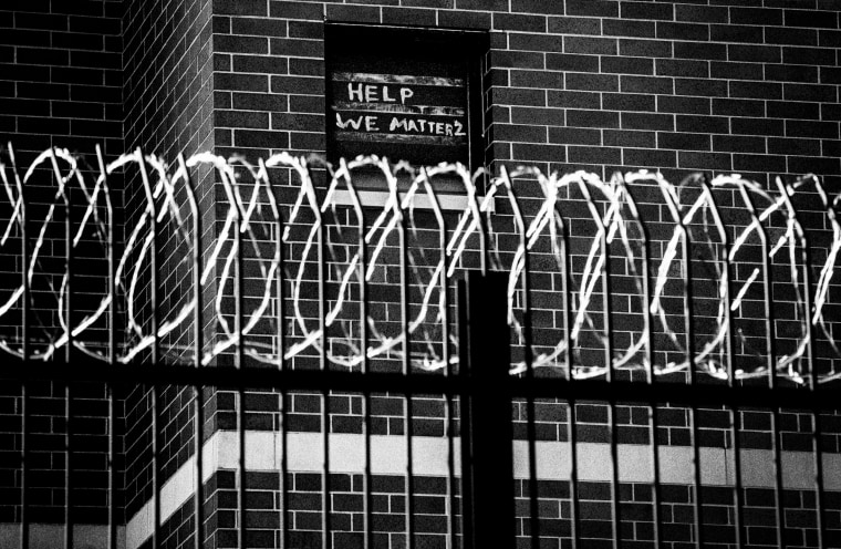 Signs made by prisoners pleading for help are seen on a window of Cook County Jail in Chicago