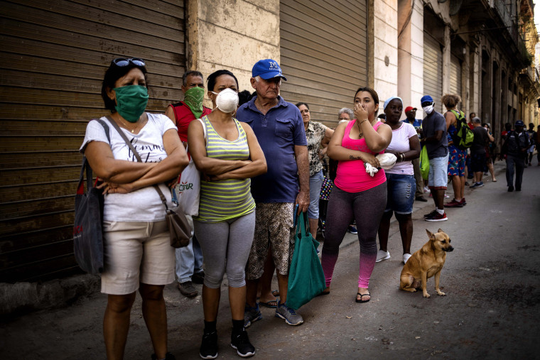 Image: People line up to buy food, some wearing protective masks as a precaution against the spread of the new coronavirus, in Havana, Cuba