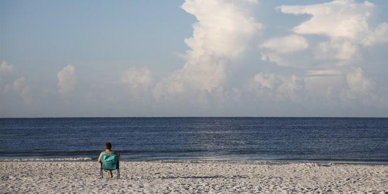 Early morning visitors sit on Siesta Beach on Aug. 26, 2018, in Siesta Key, Fla.