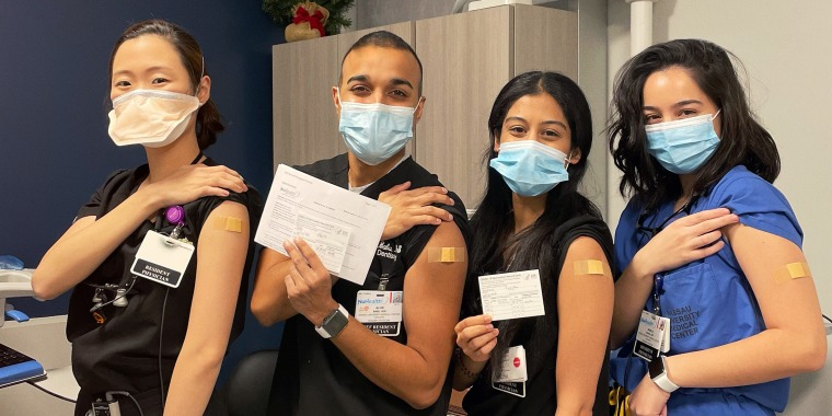 Health care workers pose with their vaccine cards following COVID-19 vaccinations.