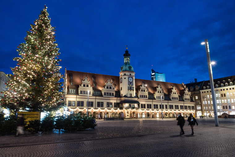Image: People walk across the almost deserted market square with decorated Christmas tree in Leipzig, eastern Germany