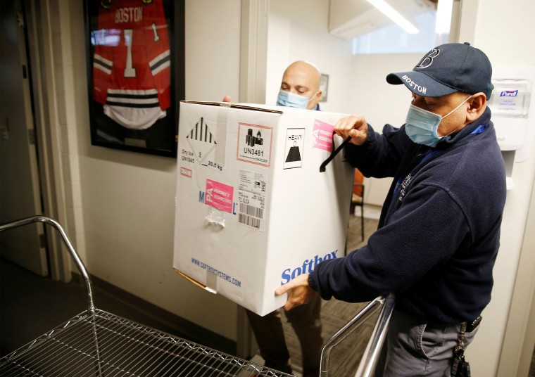 Image: Victor Ruiz (R), BMC Supply Chain Operations worker, and Richard Guarino, BMC Supply Chain Operations Associate Director, place BMC's first shipment of Pfizer's coronavirus disease (COVID-19) vaccine on a cart at Boston Medical Center in Boston, Ma