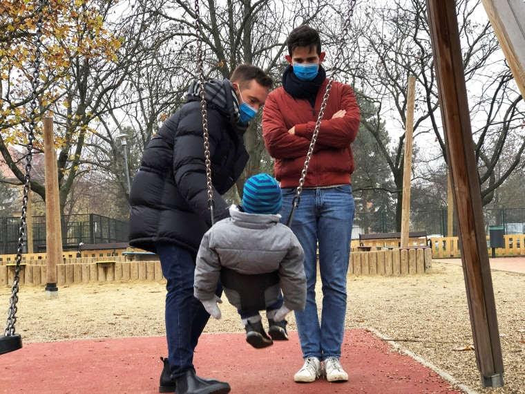 Image: Same sex couple Adam Hanol and Marton Pal play with their four year old adopted son Andras at a playground in Budapest