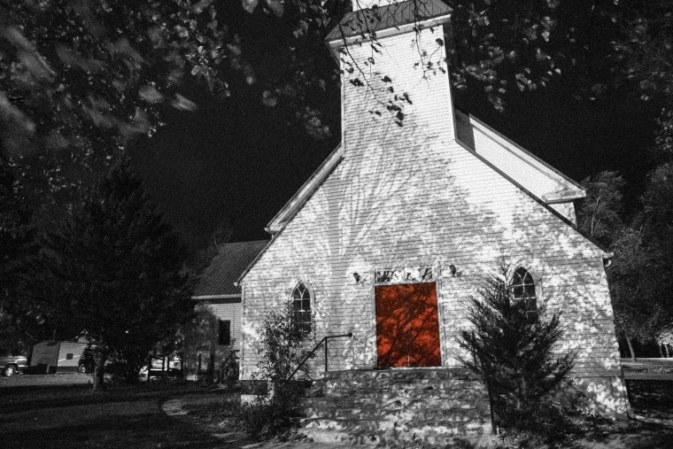 Image: A white church with a red door