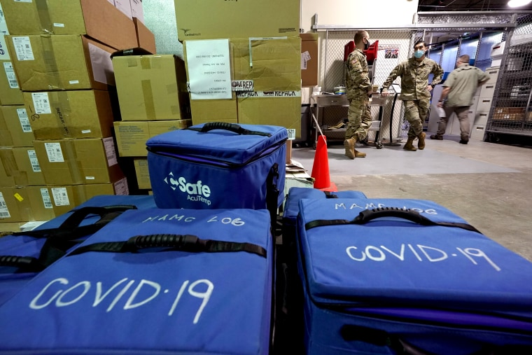 Soldiers at Madigan Army Medical Center at Joint Base Lewis-McChord in Washington state on Tuesday stand near cooler bags that will be used to transport vials of the Pfizer vaccine for Covid-19.