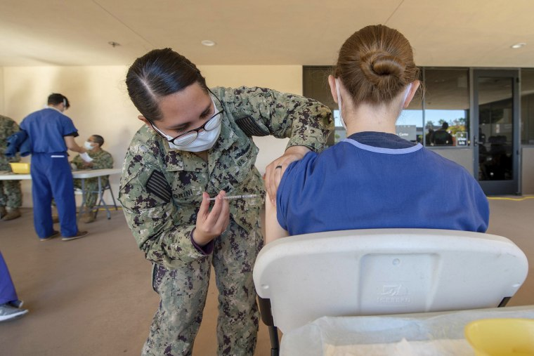 Image: A sailor assigned to Naval Medical Center San Diego (NMCSD), vaccinates a volunteering service member