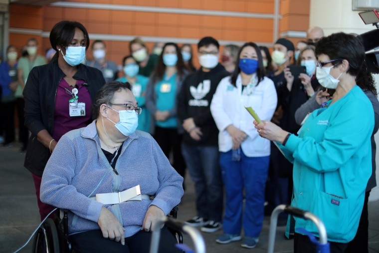 Image: A medical worker reads a poem to Daniel Kim, 48, as he leaves St. Jude Medical Center after five months after surviving the coronavirus disease in Fullerton