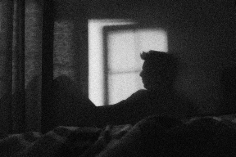 Image: A man's silhouette on the wall in a splash of sunshine from a window.