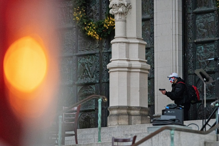 Image: A man wearing a protective mask points his guns outside the Cathedral Church of St. John the Divine in the Manhattan borough of New York City