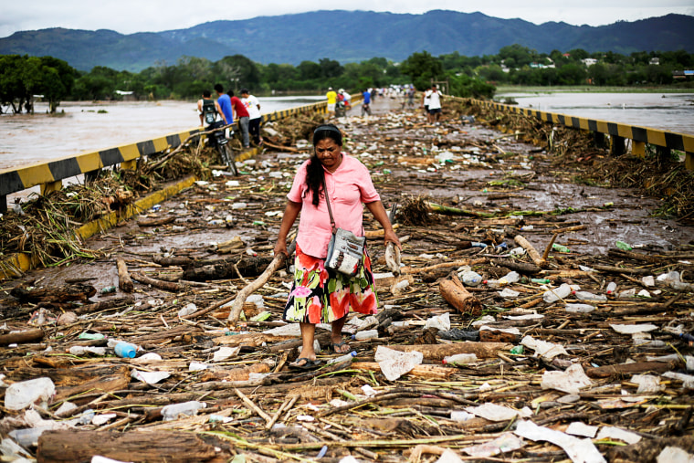 Image: FILE PHOTO: A woman walks among debris on a bridge over the Chamelecon river after the passage of Storm Eta, in Pimienta