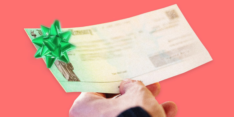 Image: A person holds a U.S. Treasury Check with a green Christmas bow on it.