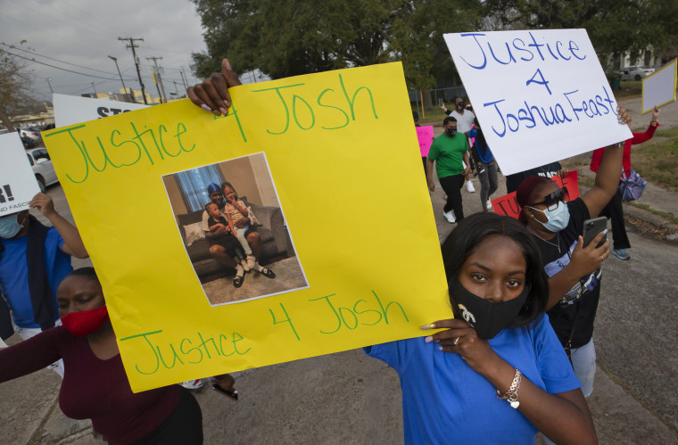 Protesters carry signs during a march in La Marque, Texas on Dec. 12 to protest the shooting of Joshua Feast by a La Marque police officer.