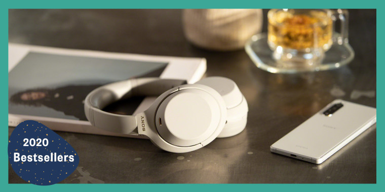 White Sony headphones on table next to tea and a magazine