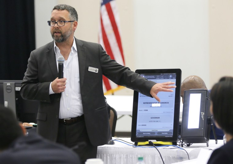 Image: Eric Coomer from Dominion Voting demonstrates his company's touch screen tablet that includes a paper audit trail at the second meeting of Secretary of State Brian Kemp's Secure, Accessible & Fair Elections Commission in Grovetown, Ga.