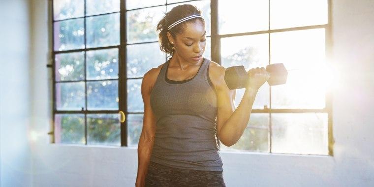 Female athlete lifting dumbbells in gym