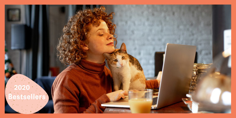 Women cuddling with her cat, while it sits on her laptop