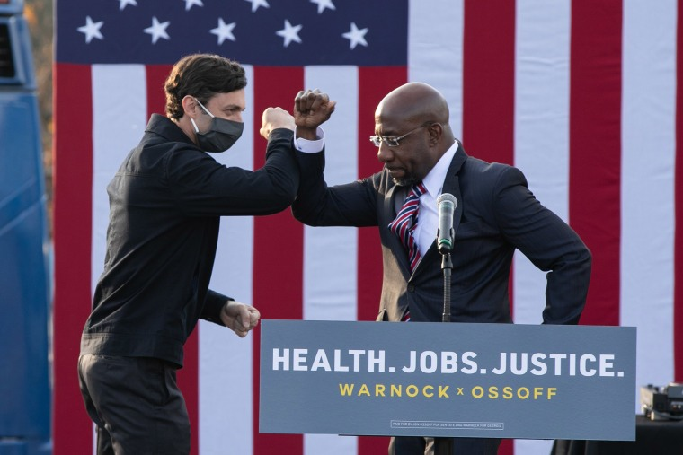 "Image: Georgia Democratic Senate candidates Raphael Warnock and Jon Ossoff bump elbows during a ""It's Time to Vote"" drive-in rally"