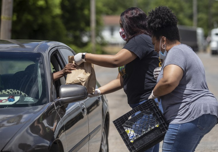 Chiquikta Fountain, right, executive director of Delta Hands for Hope, distributes food in Shaw, Miss., on May 27.