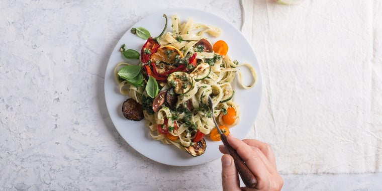 Eating Fettucine with roasted colorful vegetables and parsley  pesto
