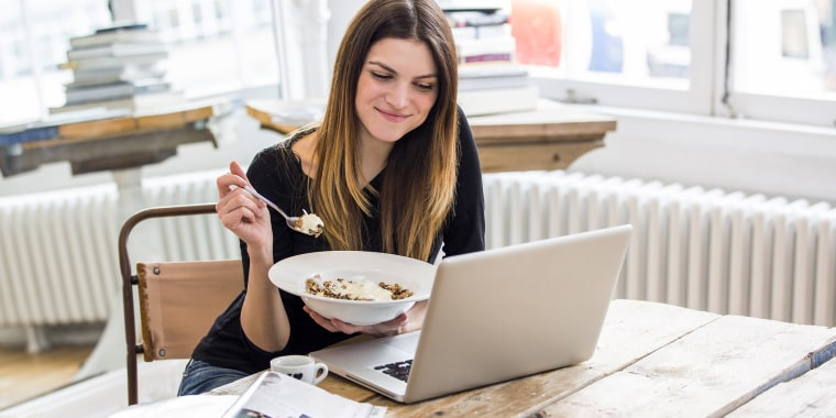 Young woman in city apartment eating muesli breakfast whilst reading laptop