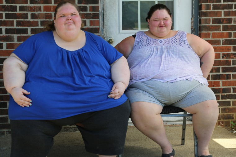 """""""1000-lb. Sisters"""" stars Tammy and Amy Slaton pose together on their front porch."""