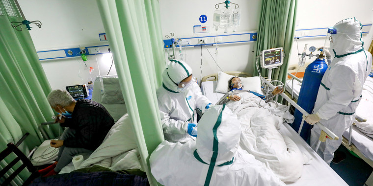 Image: Medical workers in protective suits attend to a novel coronavirus patient at an isolated ward of a designated hospital in Wuhan