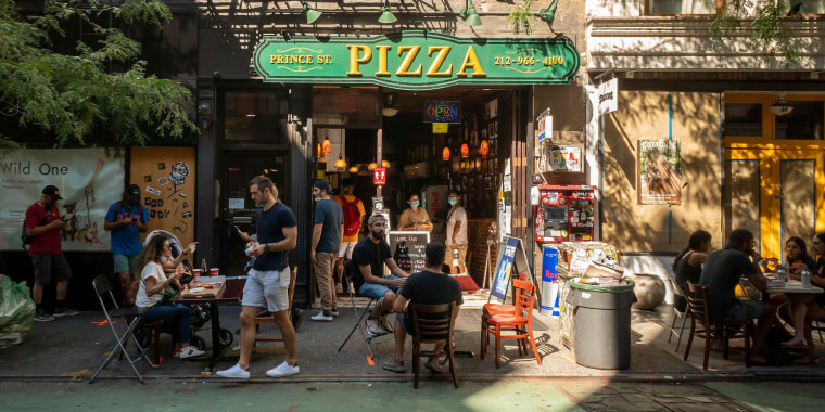 Pizza lovers practice social distancing at the al fresco dining outside the popular Prince Street Pizza in the Nolita neighborhood of New York on Sunday, August 23, 2020.