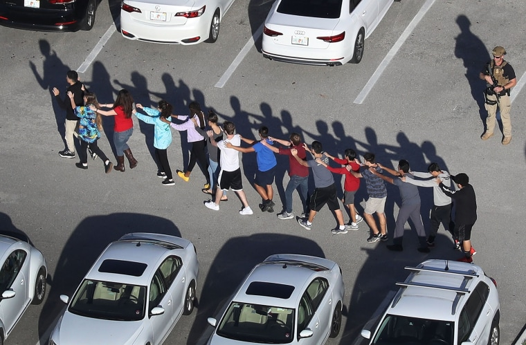 Image: People are brought out of the Marjory Stoneman Douglas High School after a shooting at the school that reportedly killed and injured multiple people