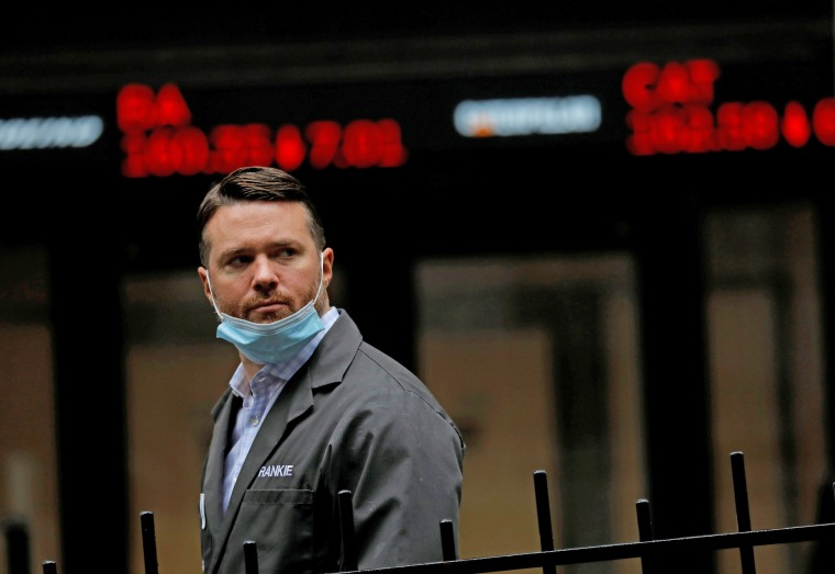 A trader walks past a digital stock price display outside the New York Stock Exchange on Oct. 26, 2020.