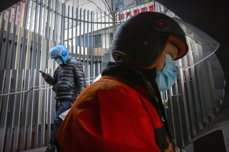 Image: Delivery drivers wearing face masks to protect against the coronavirus walk along a staircase at an office and shopping complex in Beijing