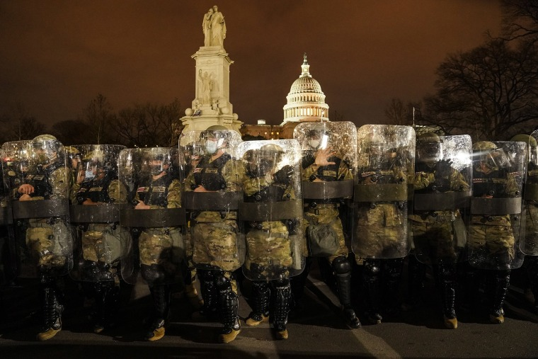 Image: District of Columbia National Guard stand outside the Capitol, Wednesday night, Jan. 6, 2021, after a day of rioting protesters.