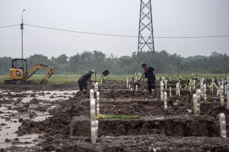 Image: Gravediggers bury a Covid-19 coronavirus victim amid pouring rain at Keputih cemetery in Surabaya, Indonesia