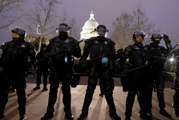 Image: Police officers in riot gear line up as protesters gather on the U.S. Capitol Building